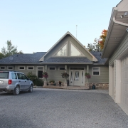 Residential project - green stone house with horizontal siding - front