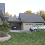 Residential project - green stone house with horizontal siding - garage