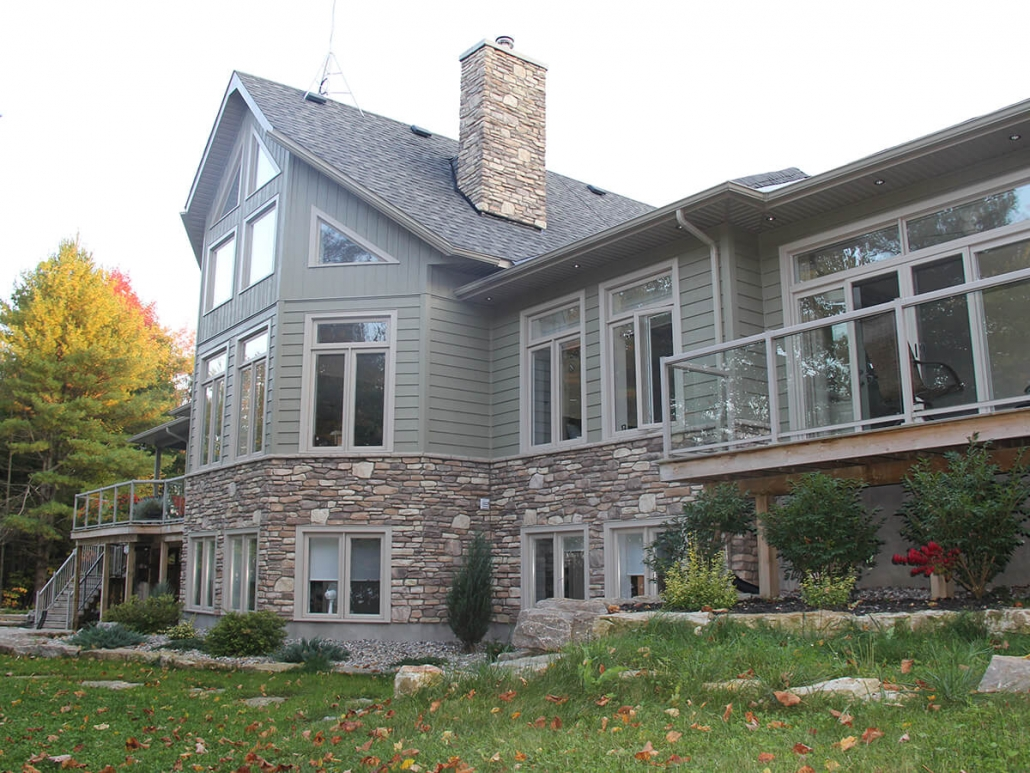 Residential project - green stone house with horizontal siding - rear view