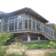 Residential project - green stone house with horizontal siding - screen-porch